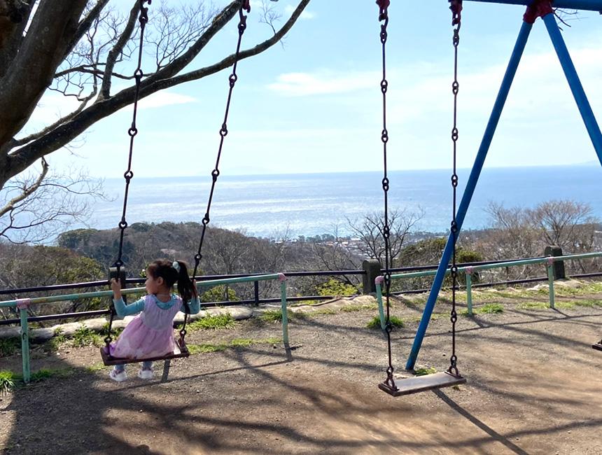 湘南平の海の見えるブランコで遊ぶ子ども