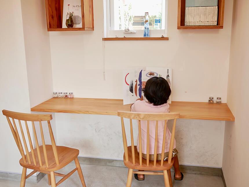 絵本を読みながら、カウンター席に座る子ども