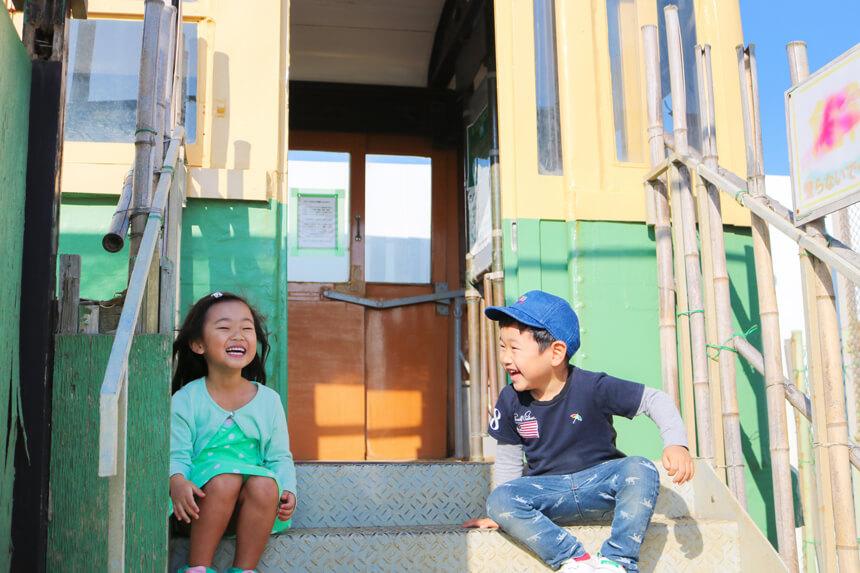 鎌倉海浜公園の江ノ電車両前で座る子ども