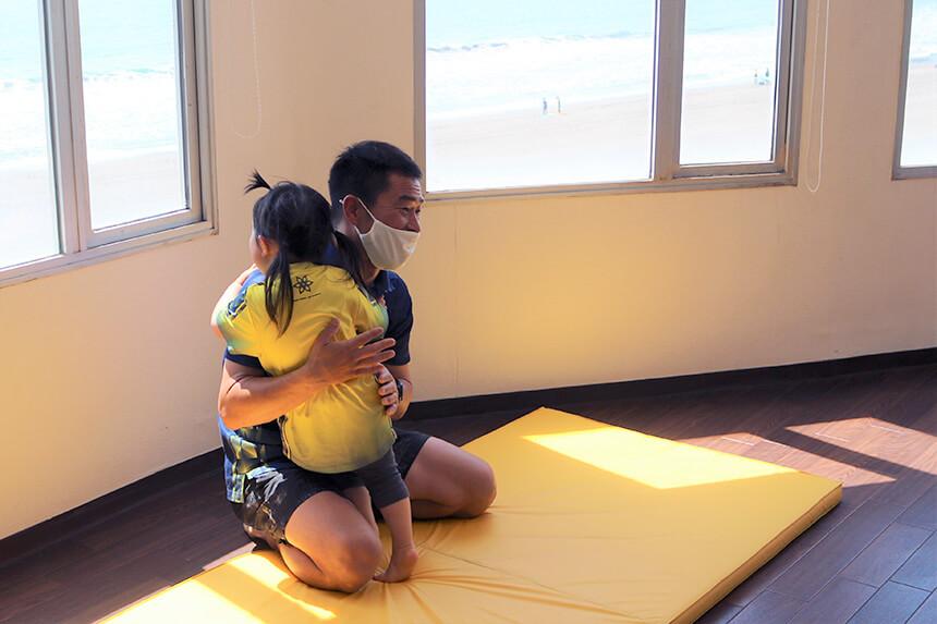 湘南の体操教室・運動教室『湘南ゴールデンエイジアカデミー』で子どもを抱っこするコーチ