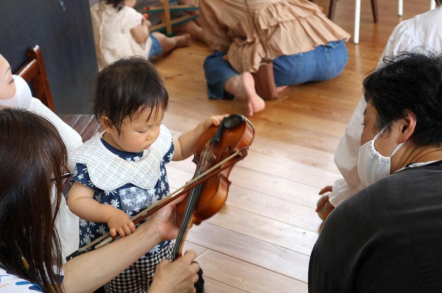 バイオリンを片手に集中する女の子