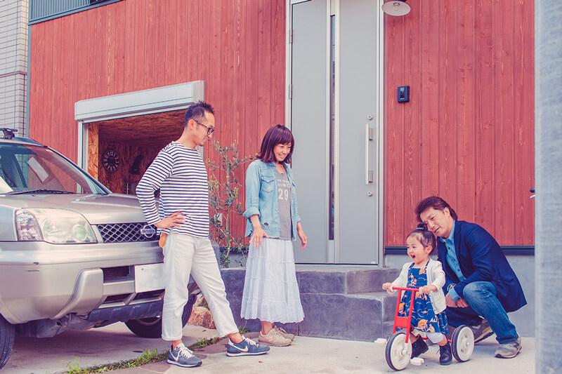 玄関ガレージの前で話す家族