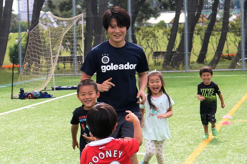 サッカーコーチと一緒に走る幼児