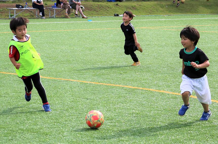 サッカーボールを追いかける男の子2人