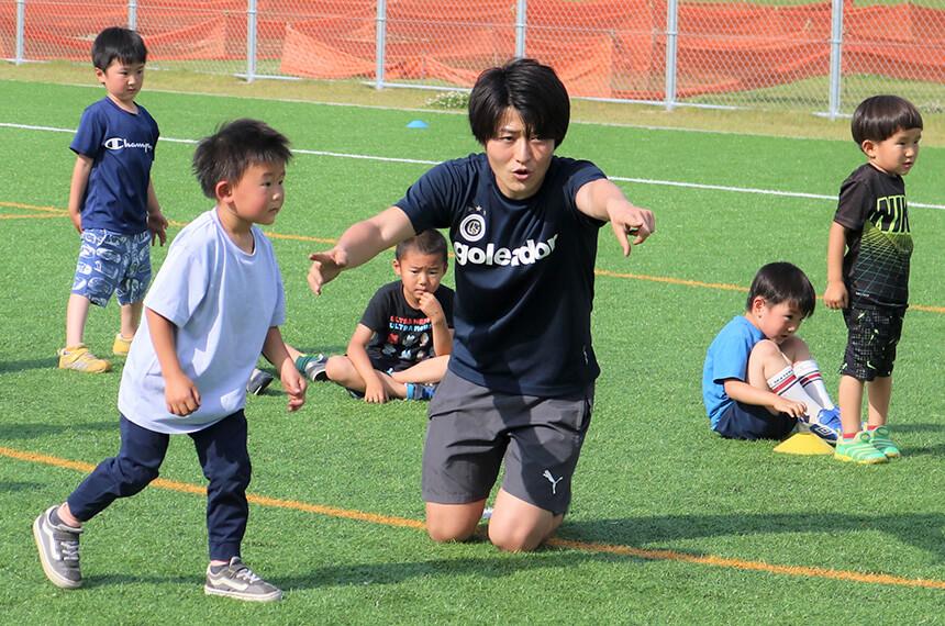 子どもにサッカーの楽しさを教えるコーチ