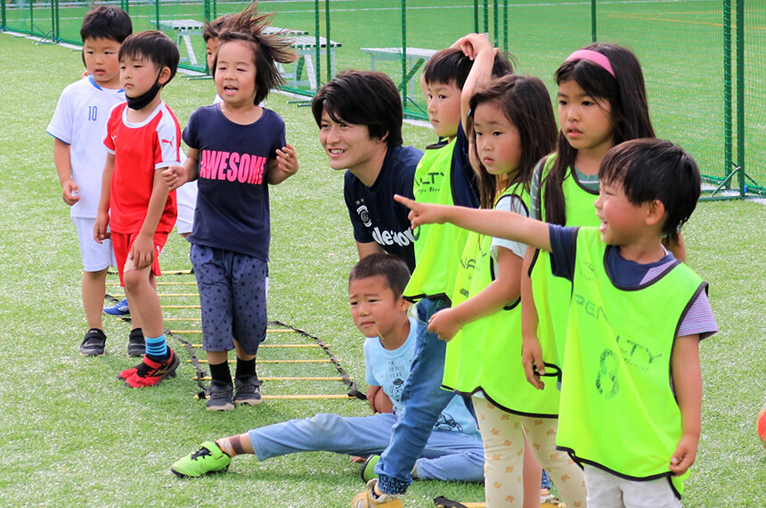 サッカークラブの子どもたちとコーチ