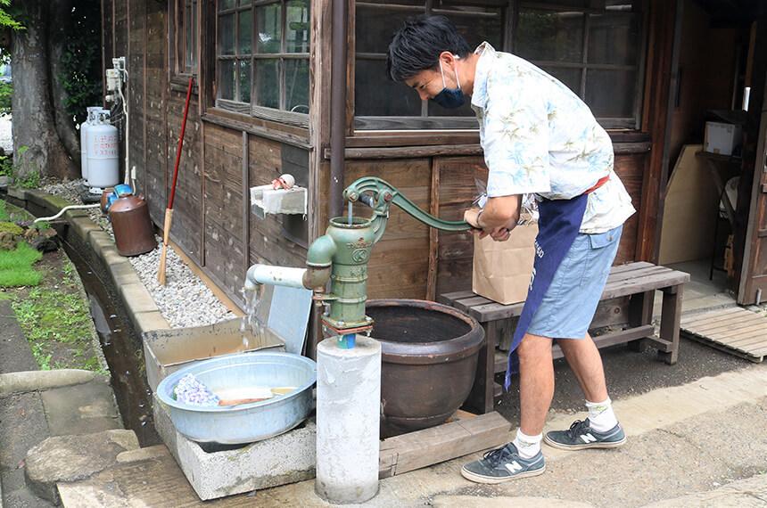 手押しの井戸から水を汲み上げるナミニココーヒーの店主