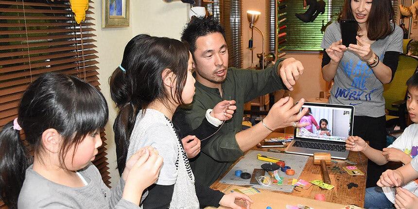 平塚イベントで革キーホルダー作りをする子ども