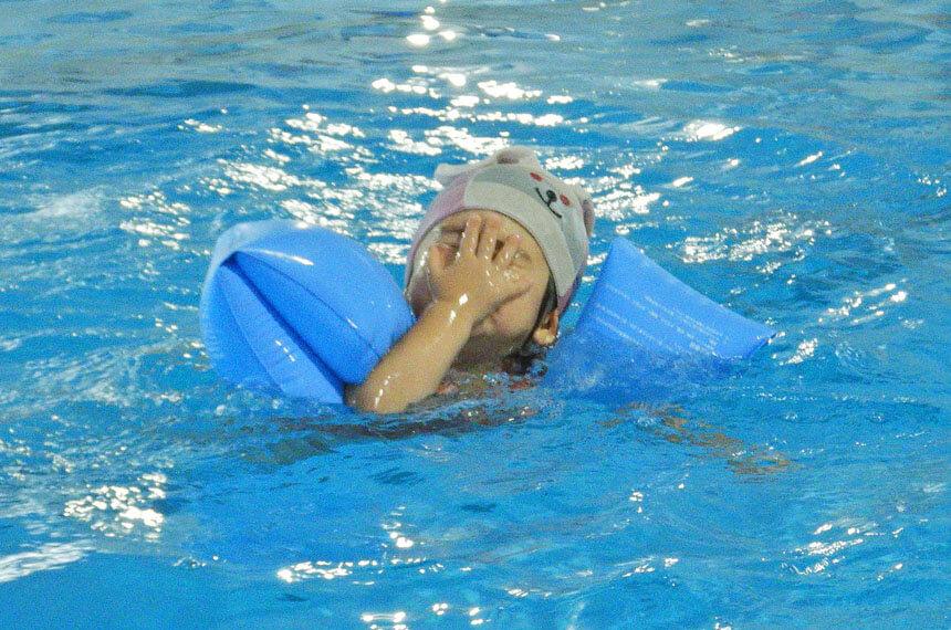 水の中で顔を覆う子ども