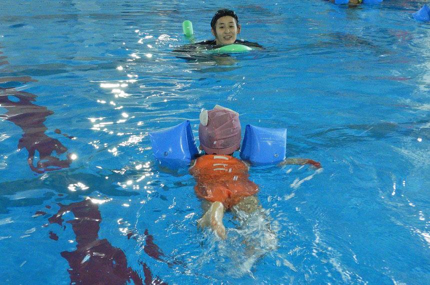 ベビースイミングのレッスンで泳ぐ子ども